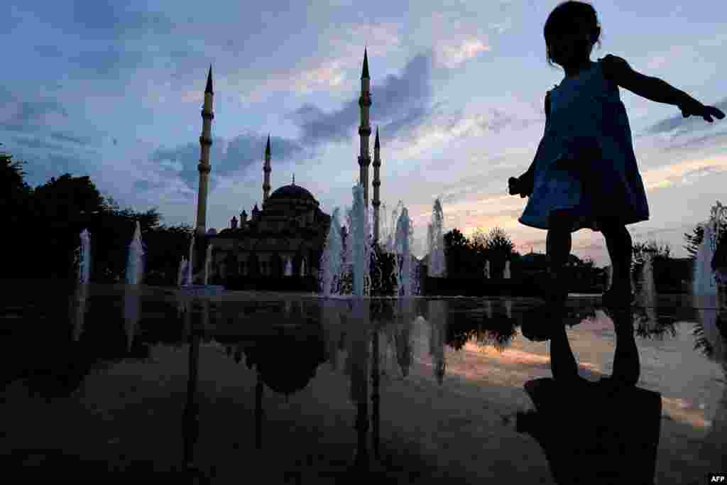 A child is seen near the fountain outside the Heart of Chechnya Mosque in central Grozny, Russia. (AFP/Kirill Kudryavtsev)