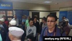 Полиция ұстаған Азаттық тілшісі Асылхан Мамашұлы (оң жақта) полиция ұстаған өзге де азаматтар Әуезов аудандық ішкі істер басқармасында. Алматы, 21 мамыр 2016 жыл.