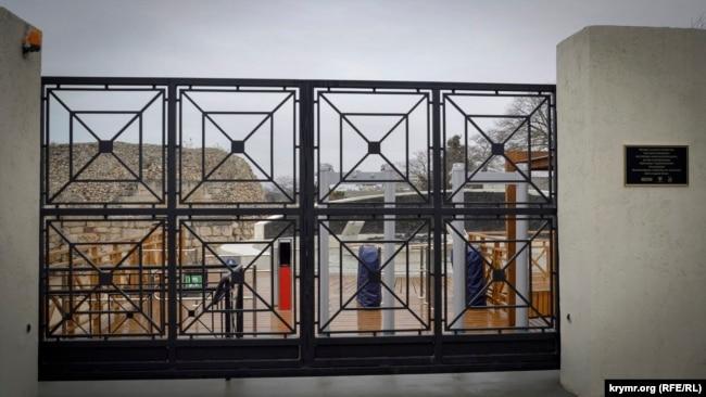 За новыми воротами с турникетами - бетонно-чугунная стела. Слева развалины башни Зенона