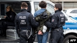 German police arrest a protester following clashes between Pro-Kurdish and Turkish demonstrators at Duesseldorf airport.