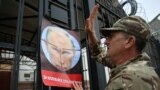 A demonstrator puts up a poster depicting Russian President Vladimir Putin during a rally to commemorate the fourth anniversary of the battle in the eastern city of Ilovaysk, in front of the Russian Embassy in Kyiv, on August 29.