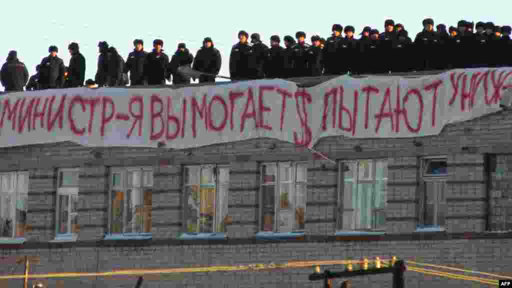 "Inmates stand on a roof of Prison No. 6 in Kopeysk with a sign that says, ""The [prison] administration extorts money and tortures us."""