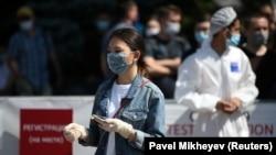 Олмаота шаҳридаги коронавирусга тест топшириш пункти ёнида турган ниқобли аёл, 2020 йил 17 июни.