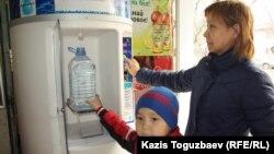 Жительница Алматы покупает очищенную питьевую воду в установленном в магазине диспенсере.