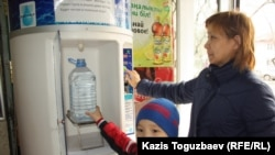 Жители Алматы набирают питьевую воду из специального диспенсера в магазине. Алматы, 12 марта 2013 года.