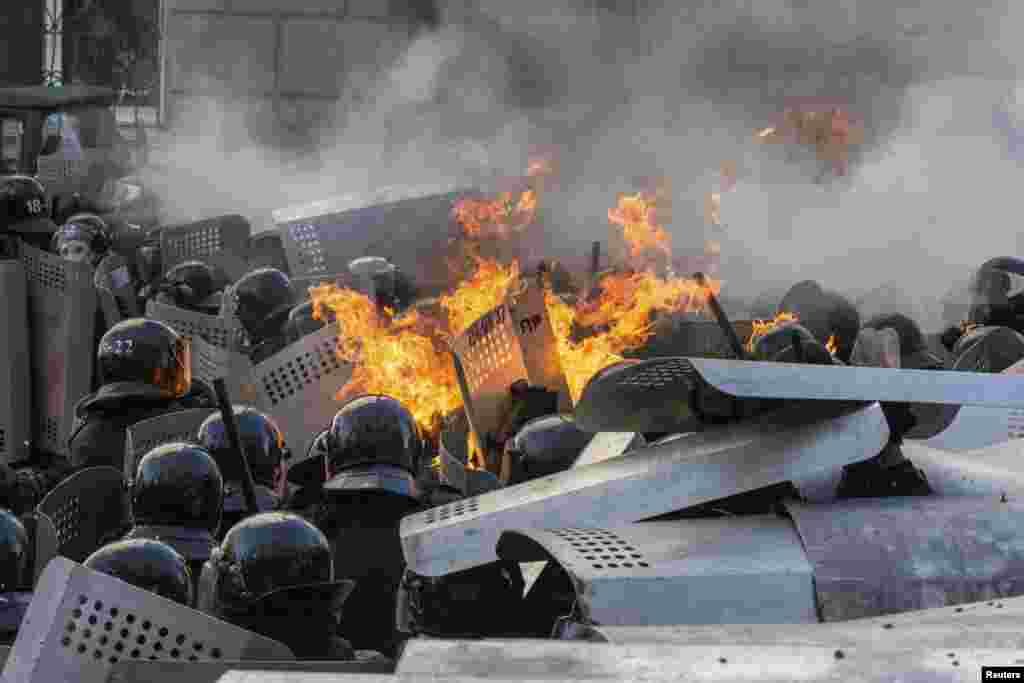 Flames rise from a group of riot police during clashes with protesters.