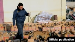 Armenia -- A photo released by the State Revenue Committee on March 3, 2021 shows an Armenian customs officer and a sniffer dog searching through boxes which authorities say contained heroin smuggled from Iran.