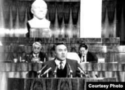 Қазақстан президенті Нұрсұлтан Назарбаев (мінберде), вице-президент Ерік Асанбаев (жоғарыда сол жақта) және Жоғары кеңес төрағасы Серікболсын Әбділдин. 1990 жылдардың бас кезіндегі сурет.