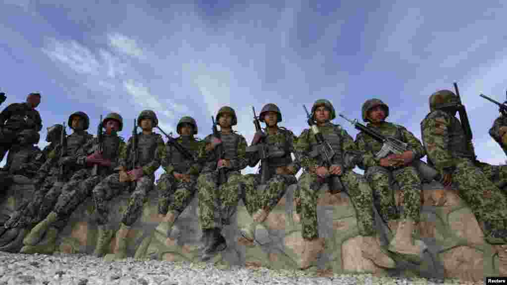 Afghan soldiers wait before a handover ceremony between the French Army and the Afghan National Army at Camp Nijrab in Kapisa Province as part of the withdrawal of French troops. French combat troops are due to pull out of Afghanistan by the end of the year. (Reuters/Eric Gaillard)