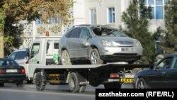 Ewakuator heläkçilige uçran ulagy alyp gidip barýar, Aşgabat, 24-nji noýabr, 2013-nji ýyl. (Illýustrasiýa suraty)
