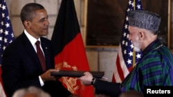 U.S. President Barack Obama (left) and his Afghan counterpart President Hamid Karzai exchange documents after signing the strategic partnership agreement at the Presidential Palace in Kabul on May 2.