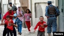 Children flee as security forces respond after several large explosions hit a busy downtown area of Kabul on May 24.