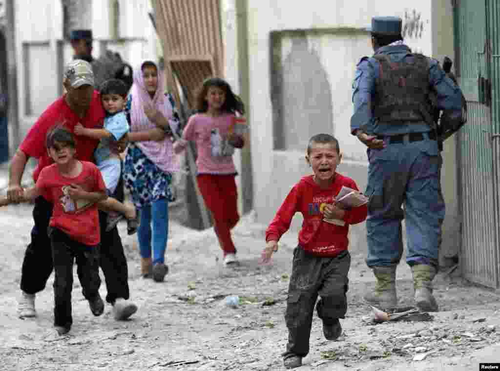Children run from the site of an explosion in Kabul on May 24.