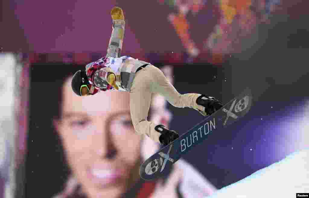 U.S. star snowboarder Shaun White jumps near a picture of himself during the men's snowboard halfpipe qualification round.