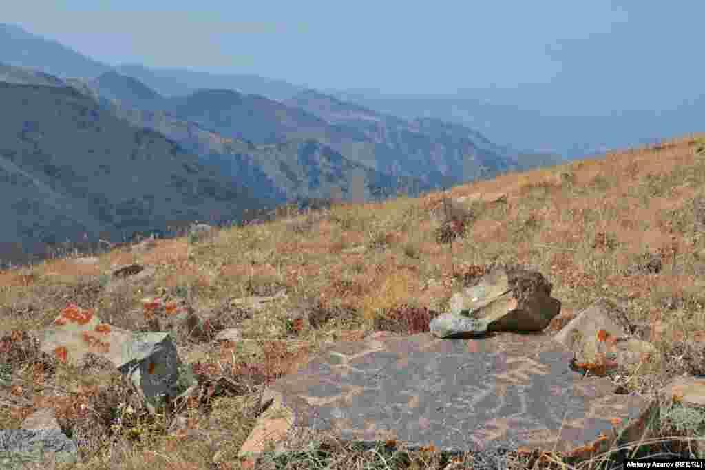 Древние наскальные рисунки встречаются уже на склоне горы Рахат. На обратном пути, 23 сентября, корреспондент Азаттыка, спускаясь с вершины Рахата после тренировочного подъема на эту гору, обнаружил на южном склоне этот камень с множеством петроглифов.