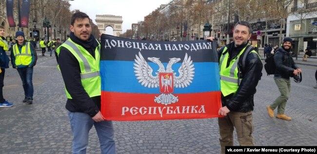 "Ксавье Моро (слева) и Фабрис Сорлен с флагом ""ДНР"" на Елисейских полях"