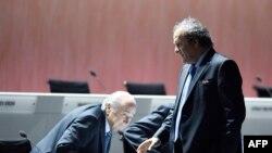 Президент УЕФА Мишель Платини (справа) проходит рядом с президентом ФИФА Йозефом Блаттером во время конгресса ФИФА. Цюрих, 29 мая 2015 года.