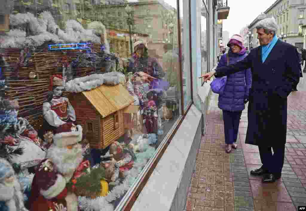 Посетивший 15 декабря Москву госсекретарь США Джон Керри у витрин одного из сувенирных магазинов российской столицы. Керри сопровождает Селеста Уолландер из Совета национальной безопасности США.