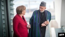 Germany -- Chancellor Angela Merkel (L) talks with Afghan President Hamid Karzai during a meeting at the Chancellery in Berlin, 16May2012