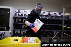 Працівник виборчої комісії виймає оброблені сортувальною машиною бюлетені для голосування поштою під час первинних внутрішньопартійних виборів у штаті Вашингтон, 4 серпня 2020 року