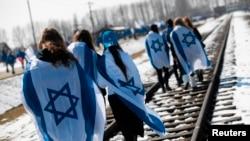 Люди c израильскими флагами на плечах идут по железнодорожным путям бывшего нацистского лагеря смерти Биркенау (Аушвиц II) в Освенциме-Бжезинку на юге Польши, 8.04.2013