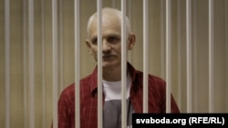 Belarusian human rights activist Ales Byalyatski stands in a guarded cage during his trial for tax evasion in Minsk.