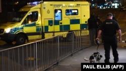 Кинолог с собакой и автомобиль экстренных служб рядом с Manchester Arena, где произошел взрыв. Манчестер, 23 мая 2017 года.