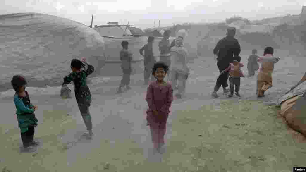 Internally displaced children shield themselves from dust picked up by wind at a refugee camp in Kabul. (Reuters/Omar Sobhani)