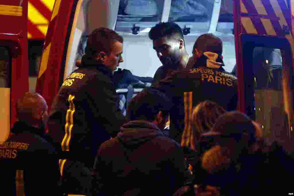 A wounded man is put into a fire truck next to the Stade de France where a number of explosions occurred in the north of Paris.