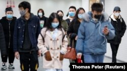 People wearing protective masks in a subway tunnel during evening rush hour in Beijing on March 10.