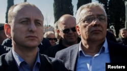 Montenegrin opposition leaders Milan Knezevic (left) and Andrija Mandic wait outside parliament on February 15.