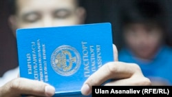 Мужчина держит в руках паспорт гражданина Кыргызстана.