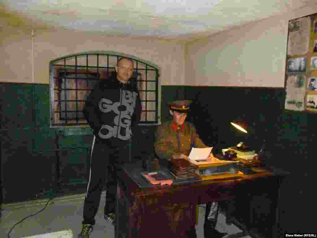 A visitor is photographed in the re-created office of a KarLAG officer, where new prisoners would be accepted and their personal files reviewed.