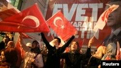 Прихильники влади святкують перемогу у столиці Анкарі з плакатами з портретами президента і словом «Evet» – «Так», 16 квітня 2017 року