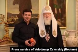 Predsjednik Volodimir Zelenski (lijevo) i patrijarh Filaret poziraju za fotografisanje tokom sastanka u Kijevu 30. aprila.