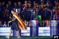 """Шави държи реч на """"Камп Ноу"""" на фона на трите трофея, спечелени от """"Барселона"""" в последния му сезон в отбора, 7 юни 2015 г."""