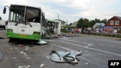 Russia -- People check the crash scene on July 13, 2013 near the village of Oznobikhino outside Moscow after at least 18 people were killed and at least 40 injured when a gravel truck smashed into a bus packed with passengers.