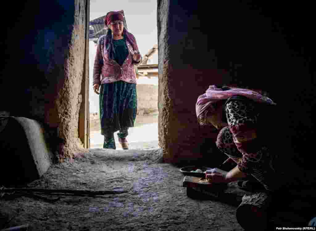 Zarina's mother supervises one of her daughters, as she prepares a salad in their kitchen.