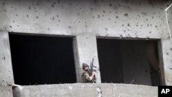 د ناټو یو سرتېری له وسلوالو طالبانو سره د نښتې پرمهال په یوې ودانۍ کې له خپل توپک سره تیار ولاړ دی.