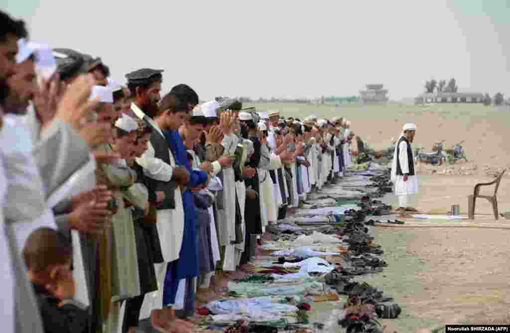 Afghan residents offer prayers at the start of Eid al-Fitr at an open air mosque on the outskirts of Jalalabad.