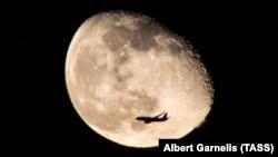 Пассажирский самолет на фоне Луны.