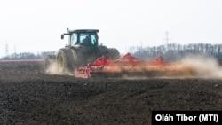 Szántóföldet boronál egy traktor.