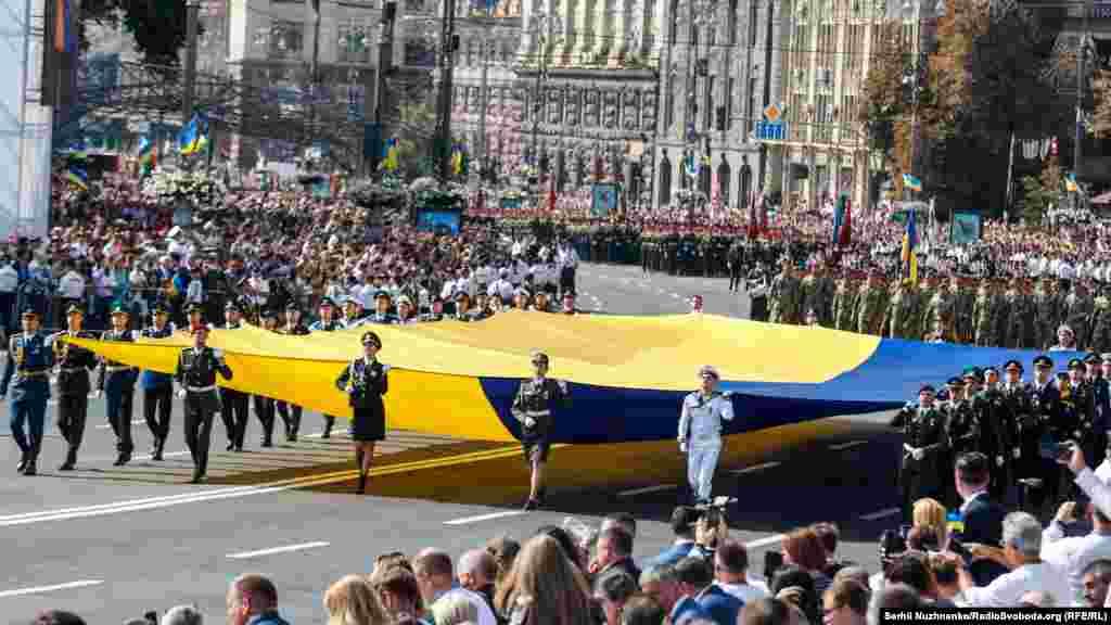 Центром столиці проносять великий Державний Прапор України. Стяг несе зведена група військових ЗСУ