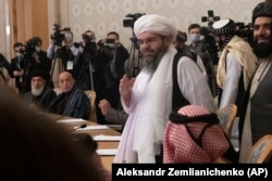 Бывший президент Афганистана Хамид Карзай (второй слева) смотрит, как члены делегации «Талибана» прибывают для участия в международной мирной конференции в Москве, 18 марта 2021 года.
