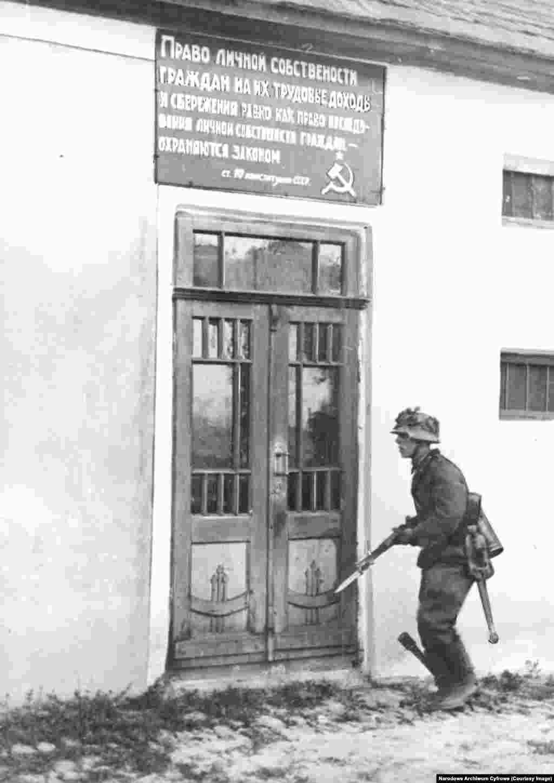 Нацистский солдат с гранатой в сапоге движется по советской деревне в июне 1941 года. Частично мотивом Барбаросса была расовая ненависть к тому, что нацистское руководство считало «нечеловеческими» славянскими народами. Согласно нацистскому «генеральному плану для Востока» большинство славян должно было быть убито или порабощено, а огромные территории Советского Союза должны были быть заселены этническими немцами.