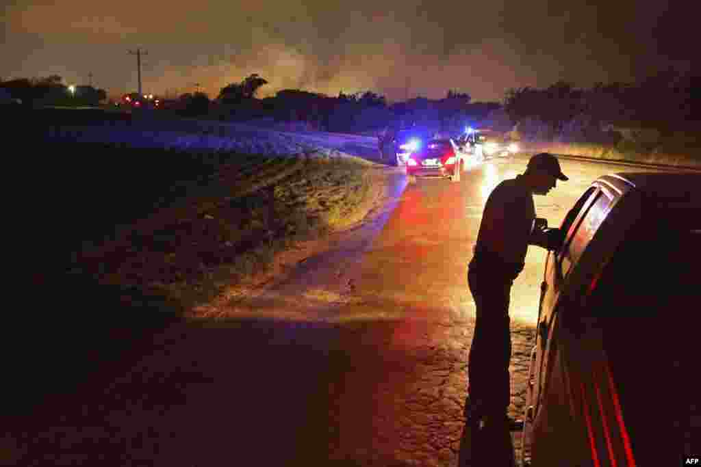A law enforcement officer at a check point in West, Texas, after a massive explosion at a fertilizer factory in the town injured more than 100 people and left damaged buildings for blocks in every direction on April 18. The death toll from the blast, which occured as firefighters were tackling a blaze, is as yet unknown. (Getty Images-AFP/Chip Somodevilla.)