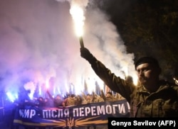 Demonstrators chant slogans and raise flares during a rally in Kiev on October 14, 2016.