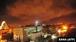 На фото видно вибухи на околиці столиці Сирії після ракетного удару США, Британії і Франції по сирійських військово-хімічних об'єктах. Дамаск, 14 квітня 2018 року
