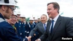 """Дэвид Кэмерон (сол жақта) мен Нұрсұлтан Назарбаев """"Болашақ"""" зауытының жұмысшыларымен кездесуде. Атырау облысы, 30 маусым 2013 жыл."""