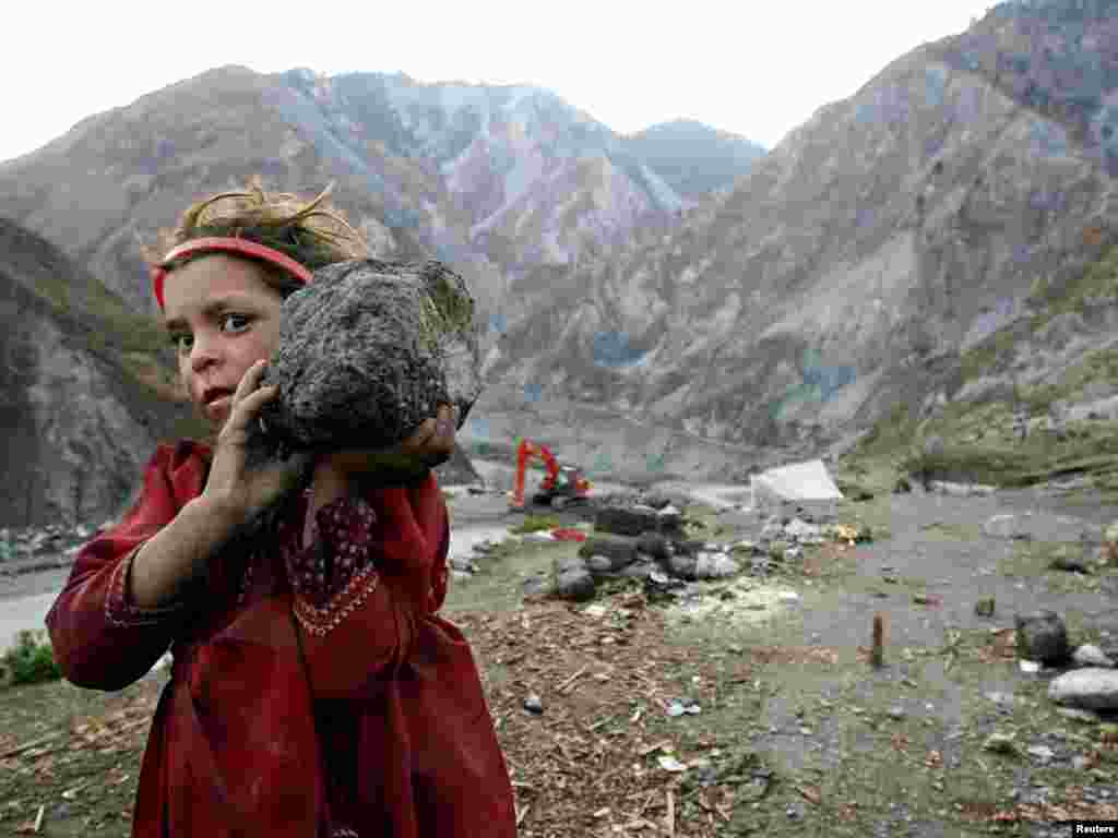 A Kashmiri girl refugee carries a stone to helps her father to build a wall in the Neelum Valley near Kamsar camp, some 10 km (6 miles) north of the earthquake-devastated city of Muzaffarabad in Pakistan-administered Kashmir February 15, 2006. Winter weather has made life more difficult for survivors of last year's massive earthquake in South Asia, where more than two million people have been living in tents or crude shelters patched together from ruined homes. REUTERS/Thierry Roge